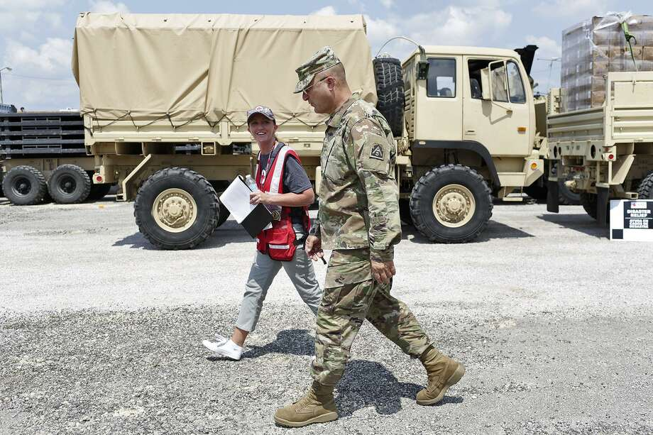 Maj. Gen. Brian Harris, commander for Joint Forces Land Component Command Forward,  talks with Jolene Carpenter, the American Red Cross coordinator for the site, Monday in Hempstead. Photo: Lisa Krantz /San Antonio Express-News / SAN ANTONIO EXPRESS-NEWS