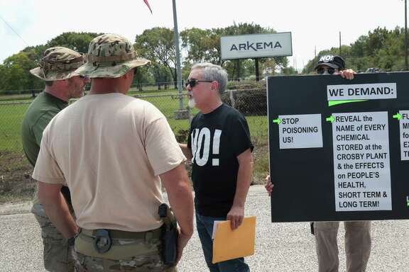 FBI agents confront protesters at the gate of the Arkema plant on Monday. One activist accused the company of poisoning the community and wants the firm to provide free medial care to those affected.