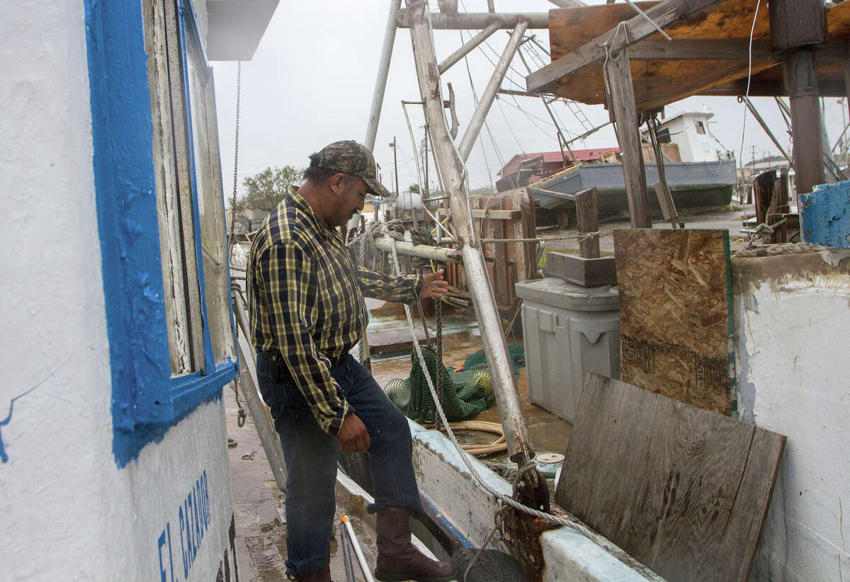 """Edward Torres checks the lines on his shrimp and oyster boat, harbored in the Seadrift, Texas docks, to make sure they're secure Monday, Aug. 28, 2017, after Tropical Storm Harvey went through the area. Other boats weren't tied down well enough and ended up on land. """"My boat is OK,"""" Torres said. """"But a lot of people don't have boats and I feel very bad because it costs very much to put them back in the water."""" (The Victoria Advocate via AP)"""
