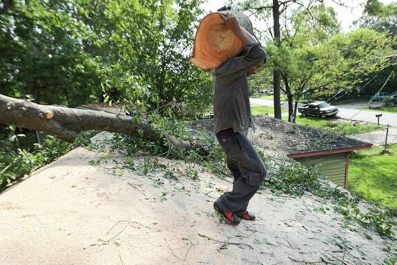 Arbor King Tree Service employee Jobany Berrios removes a tree stump from a roof of a home on  Monday, Sept. 4, 2017, in Houston in the aftermath of Tropical Storm Harvey.