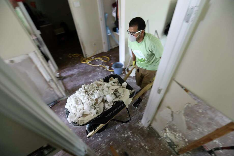 Texas Southern University graduate  student Ali Alshehri takes out a wheelbarrow filled with insulation from a home damaged by Tropical Storm Harvey on  Monday, Sept. 4, 2017, in Houston. Photo: Elizabeth Conley, Houston Chronicle / © 2017 Houston Chronicle