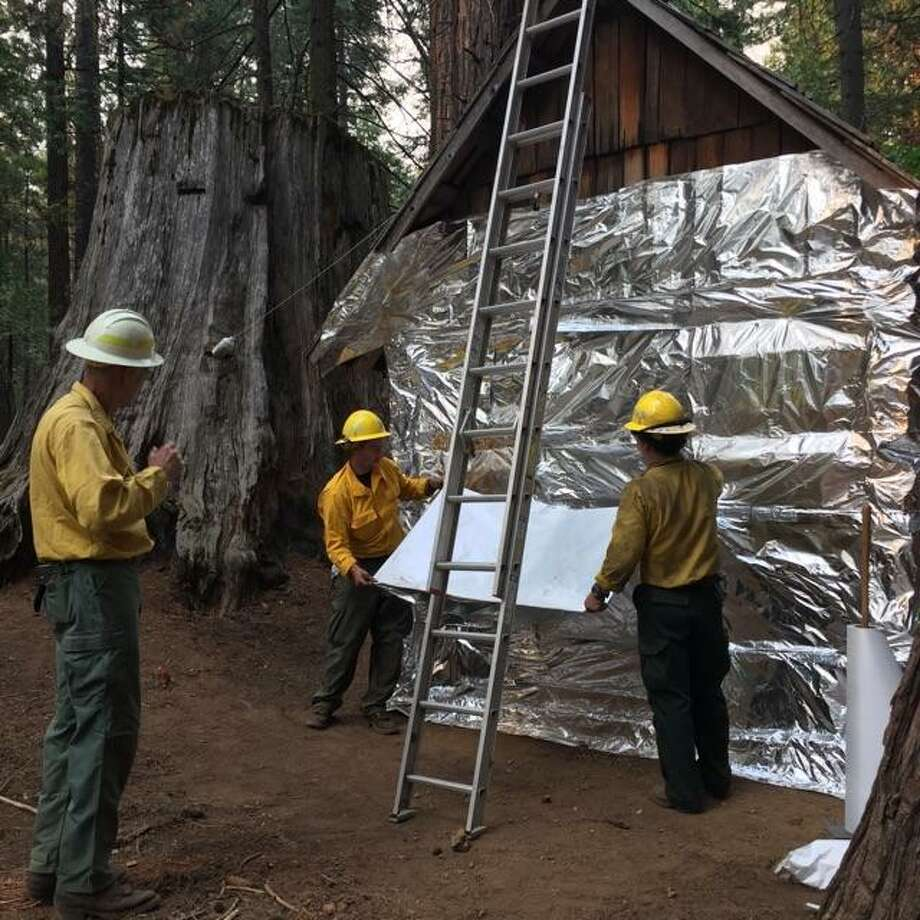 A structure is wrapped by Engine 42 to protect it from the Railroad Fire in the Sierra National Forest. Photo: United States Forest Service
