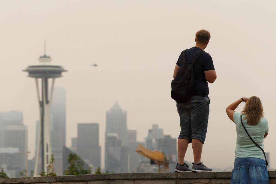 People take pictures of the Space Needle and the smokey Seattle skyline from Kerry Park on Sept. 5, 2017. Photo: Grant Hindsley/SeattlePI