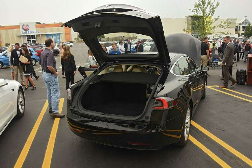 People check out Tesla cars charging up at the largest Supercharger in the Northeast during a ribbon cutting ceremony at Crossgates Mall on Tuesday, Sept. 5, 2017 in Guilderland, N.Y. Senator George Amedore and others addressed the economic benefits of Tesla's investment in the Capital Region and the environmental benefits of expanding New Yorkers' access to zero-emissions vehicles. (Lori Van Buren / Times Union)
