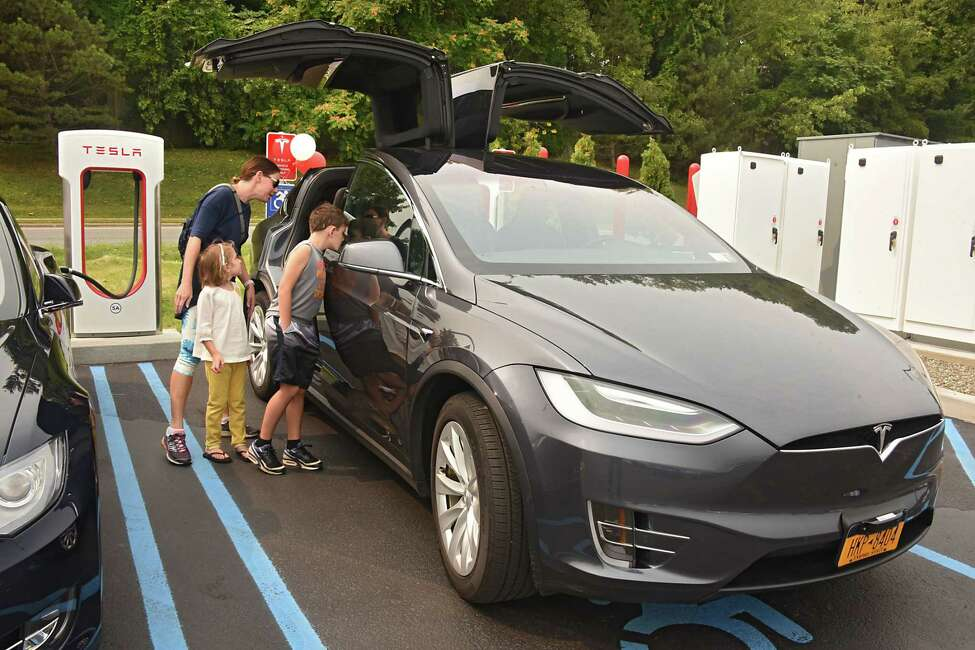 Bridgette Akins of Slingerlands and her children Jack, 8, and Eva, 5, check out a Tesla car charging up at the largest Supercharger in the Northeast during a ribbon cutting ceremony at Crossgates Mall on Tuesday, Sept. 5, 2017 in Guilderland, N.Y. Senator George Amedore and others addressed the economic benefits of Tesla's investment in the Capital Region and the environmental benefits of expanding New Yorkers' access to zero-emissions vehicles. (Lori Van Buren / Times Union)