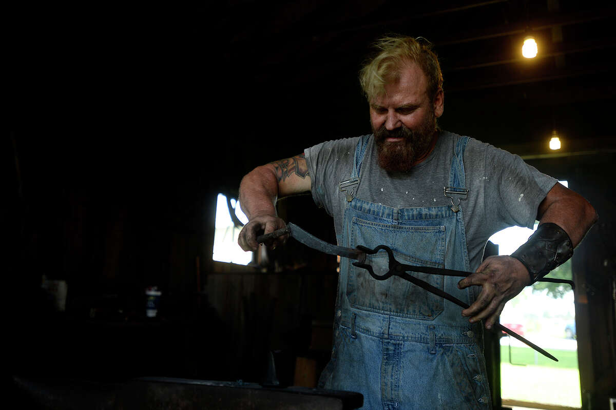 Blacksmith Rob Flurry holds a railroad spike being made into a knife during a bladesmithing class at the Spindletop-Gladys City Boomtown Museum on Saturday. Photo taken Saturday 9/24/16 Ryan Pelham/The Enterprise