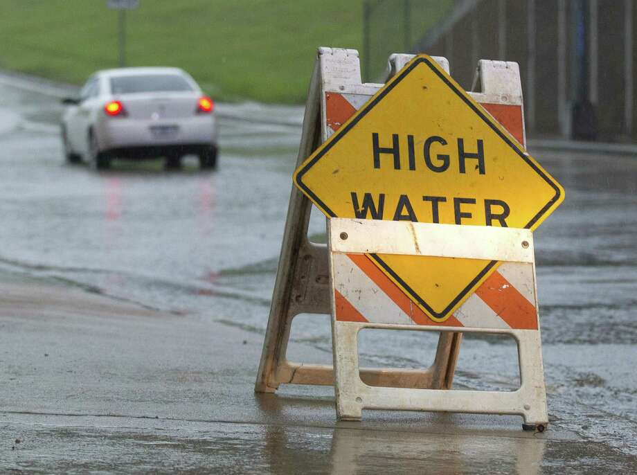 A sign warns drivers of high water on the east bound side South Loop 336 near Frazier Street after a woman drove her car through high water, Saturday, Aug. 26, 2017, in Conroe. Photo: Jason Fochtman / Houston Chronicle / Internal
