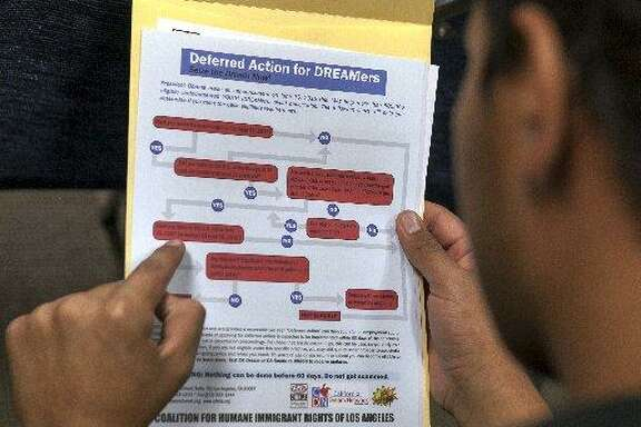 A man reads a guide of the conditions needed to apply for the Obama program known as Deferred Action for Childhood Arrivals (DACA) at the Coalition for Humane Immigrant Rights in Los Angeles.
