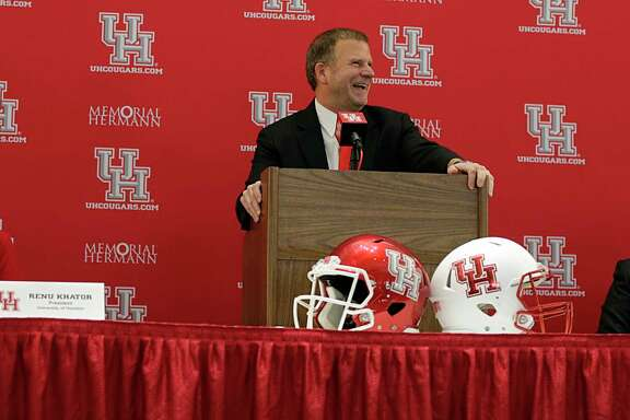 University of Houston Board of Regent Chairman Tillman Fertitta center, speaks as U of H President Renu Khator left, and Major Applewhite right, look on during a press conference announcing Applewhite as the next University of Houston football head coach at TDECU Stadium Dec. 12, 2016, in Houston. ( James Nielsen / Houston Chronicle )