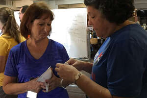 Memorial Lutheran Church - Katy volunteer Sherry Jatzlau, left, gives a mask to volunteer Susan Hooper before they head out as part of a team to help a family clean their house damaged by flood waters. They wear masks to protect themselves from mold.