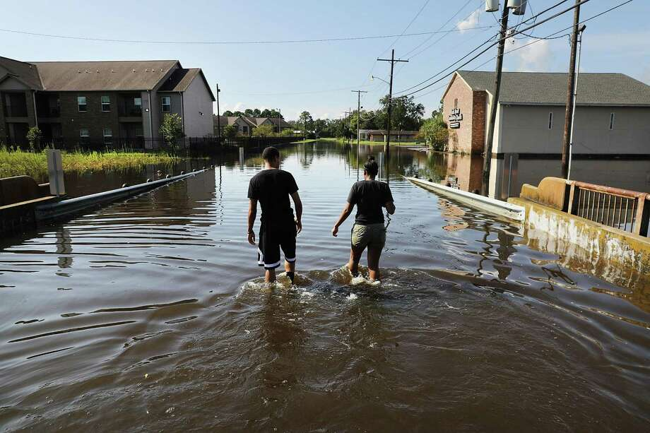 A couple walk through their flooded neighborhood as Texas slowly moves toward recovery from the devastation of Hurricane Harvey on Tuesday in Orange. U.S. companies have pledged at least $160 million to Harvey relief efforts. Photo: Spencer Platt /Getty Images / 2017 Getty Images