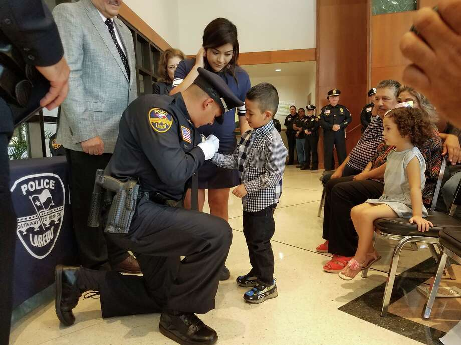 Derek D. Sanchez pins his father, Officer Luis Daniel Sanchez Jr., as his mother Mayra Sanchez witness the special moment during a pinning of the badge ceremony held Friday at Laredo police headquarters.  Photo: Courtesy