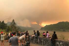 Onlookers watch the Eagle Creek Fire burn in the Columbia River Gorge on Monday, Sept. 4, 2017.