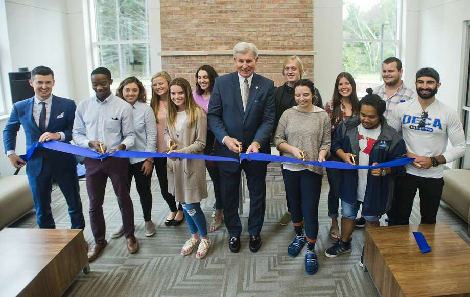 Northwood University President and CEO Keith Pretty, center, is assisted by a group of Northwood students during a ribbon-cutting ceremony inside North Village Apartments, the first new student housing to be built at the university in 37 years, on Tuesday, September 5, 2017. Photo: (Katy Kildee/kkildee@mdn.net)