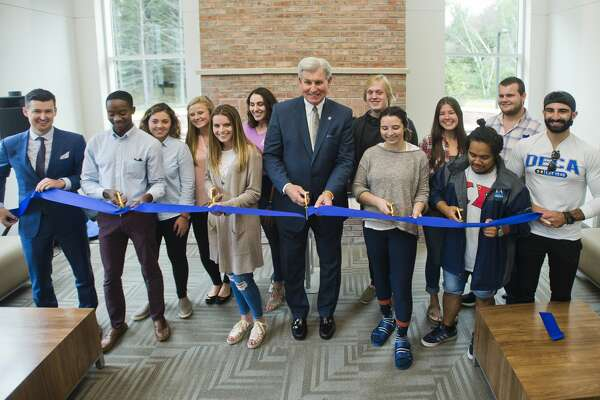 Northwood University President and CEO Keith Pretty, center, is assisted by a group of Northwood students during a ribbon-cutting ceremony inside North Village Apartments, the first new student housing to be built at the university in 37 years, on Tuesday, September 5, 2017.