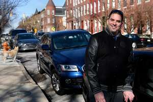 Patrick Campbell stands near his BMW and Audi cars, which he rents out with the Turo ride sharing service, on March 17, 2017, in Baltimore. (Barbara Haddock Taylor/Baltimore Sun/TNS)