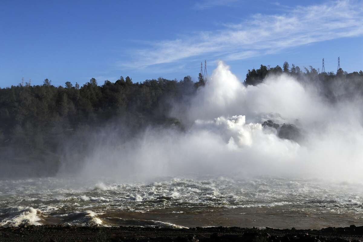 FILE - In this Feb. 14, 2017, file photo, water gushes from the Oroville Dam's main spillway in Oroville, Calif. An independent team of dam experts says bad design and construction a half-century ago contributed to a disastrous spillway collapse at the nation's tallest dam. Dam-safety experts investigating February's spillway failures at the Oroville Dam say California should have assessed the original flaws. (AP Photo/Marcio Jose Sanchez, File)