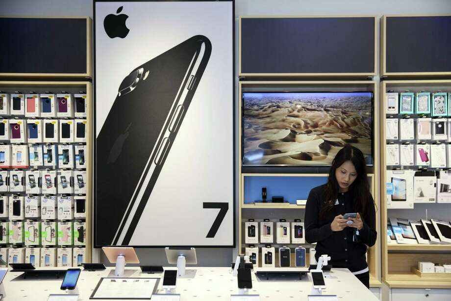 An employee uses an Apple inc. iPhone at an AT&T Inc. store in Newport Beach, Calif. Apple is about three-fourths of the way through a program that's returning $300 billion of capital to shareholders by the end of March 2019. Photo: Patrick T. Fallon /Bloomberg / © 2017 Bloomberg Finance LP