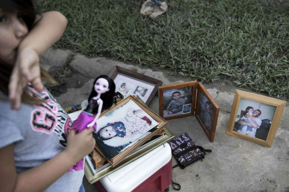 A child stands with a doll near family photos while items are salvaged from a flooded house as residents begin the recovery process from Hurricane Harvey August 31, 2017 in Houston, Texas. / AFP PHOTO / Brendan SmialowskiBRENDAN SMIALOWSKI/AFP/Getty Images ORG XMIT: MER2017083120215867 Photo: BRENDAN SMIALOWSKI / AFP or licensors
