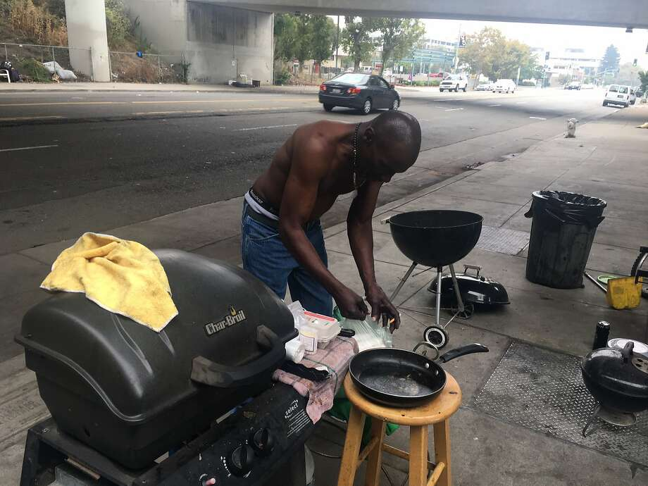 Robert Cooper, 60, prepares the grill for a Labor Day cookout at a well-kept homeless camp on Telegraph Avenue in Oakland. Photo: Otis R. Taylor Jr.