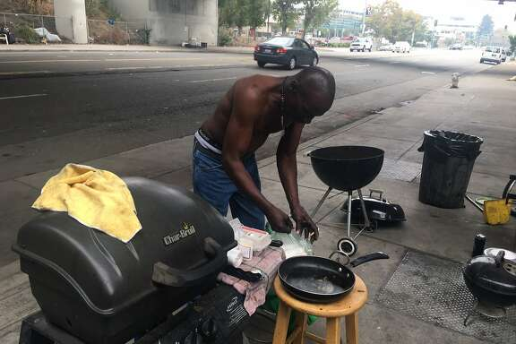 Robert Cooper, 60, prepares the grill for a Labor Day cookout at a homeless camp on Telegraph Avenue. The camp stands out because of how clean the residents keep it. One of the rules of a camp is that the sidewalk must be passable. And the sidewalk is swept daily.