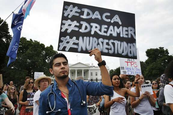 Carlos Esteban, 31, of Woodbridge, Va., a nursing student and recipient of Deferred Action for Childhood Arrivals, known as DACA, rallies with others in support of DACA outside of the White House, in Washington, Tuesday, Sept. 5, 2017. President Donald Trump began dismantling the government program protecting hundreds of thousands of young immigrants who were brought into the country illegally as children. (AP Photo/Jacquelyn Martin)