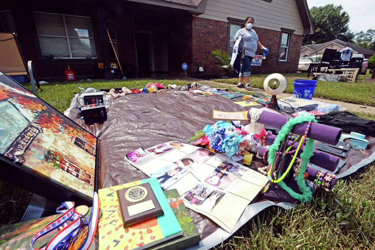 Laura Morales carries personal items to be dried on a tarp in her Northwest Forest yard on Tuesday. Residents were allowed back into the area Tuesday morning to begin cleaning out their homes. Photo taken Tuesday, September 05, 2017 Guiseppe Barranco/The Enterprise