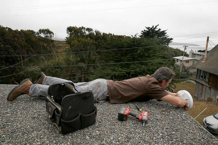 Brandt Kuykendall sprawls out on a neighbor's roof to adjust a piece of equipment for his Dillon Beach Internet Service. Photo: Liz Hafalia, The Chronicle