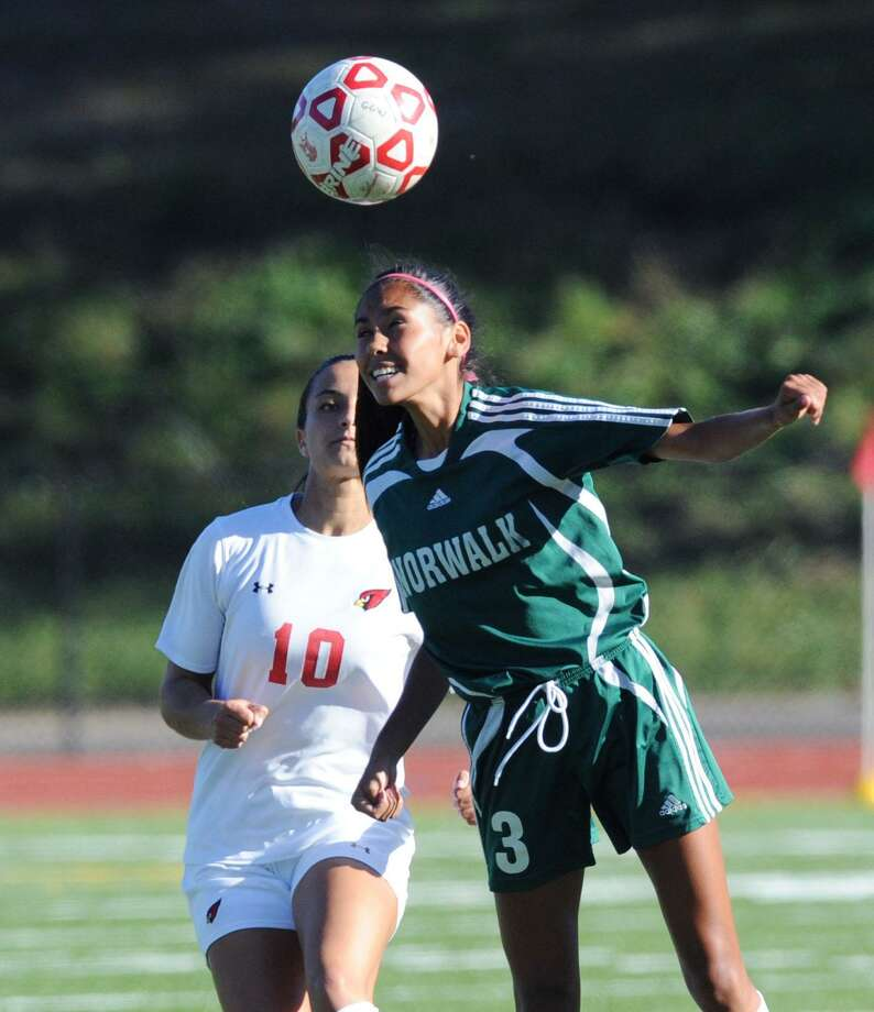 At right, Norwalk's Stephany Escalante heads as Madison Arnold (#10) of Greenwich, left, looks on during the girls high school soccer match between Greenwich High School and Norwalk High School at Greenwich, Conn., Thursday, Oct. 6, 2016. Greenwich won the match 2-1. Photo: Bob Luckey Jr. / Hearst Connecticut Media / Greenwich Time
