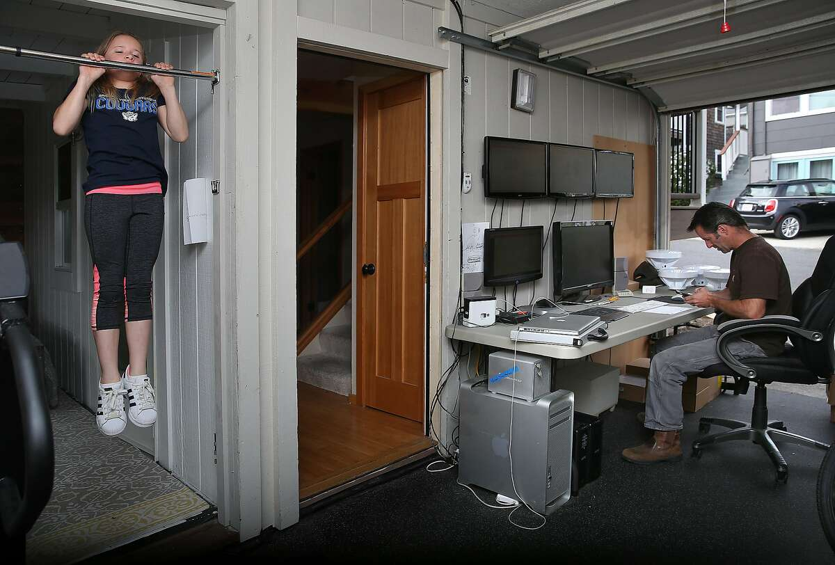Gymnast Jill Kuykendall (left), 11, does pull-ups as her dad Brandt Kuykendall (right) checks internet access for his neighbors in his basement office on Thursday, August 24, 2017, in Dillon Beach, Calif.