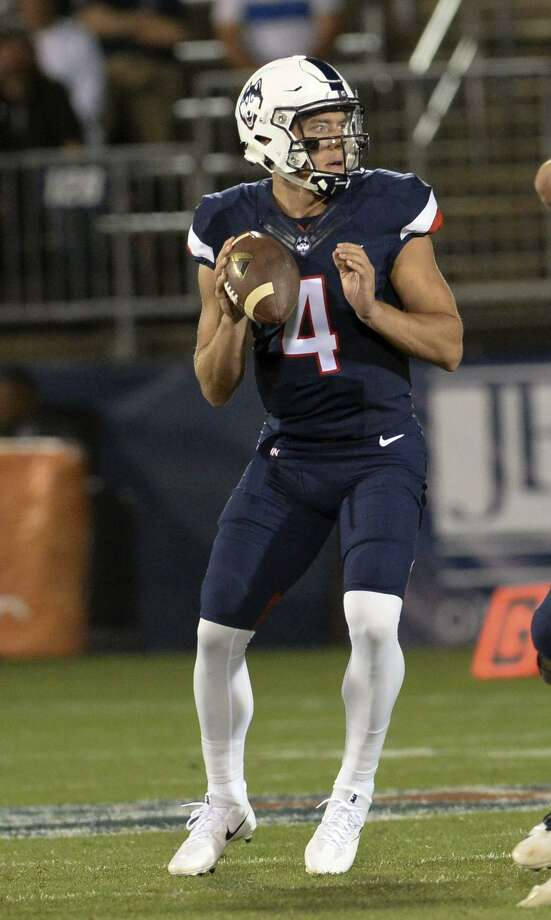 UConn quarterback Bryant Shirreffs looks for his target during the season opener against Holy Cross on Thursday in East Hartford. Photo: Stephen Dunn / Associated Press / FR171426 AP