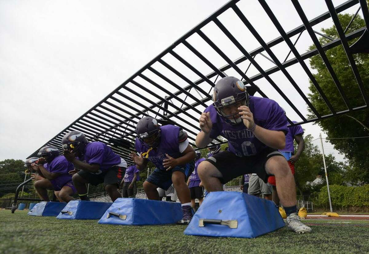 Westhill's left tackle Jack Willianson, right, works during a blocking drill at a team practice at the school Saturday in Stamford.