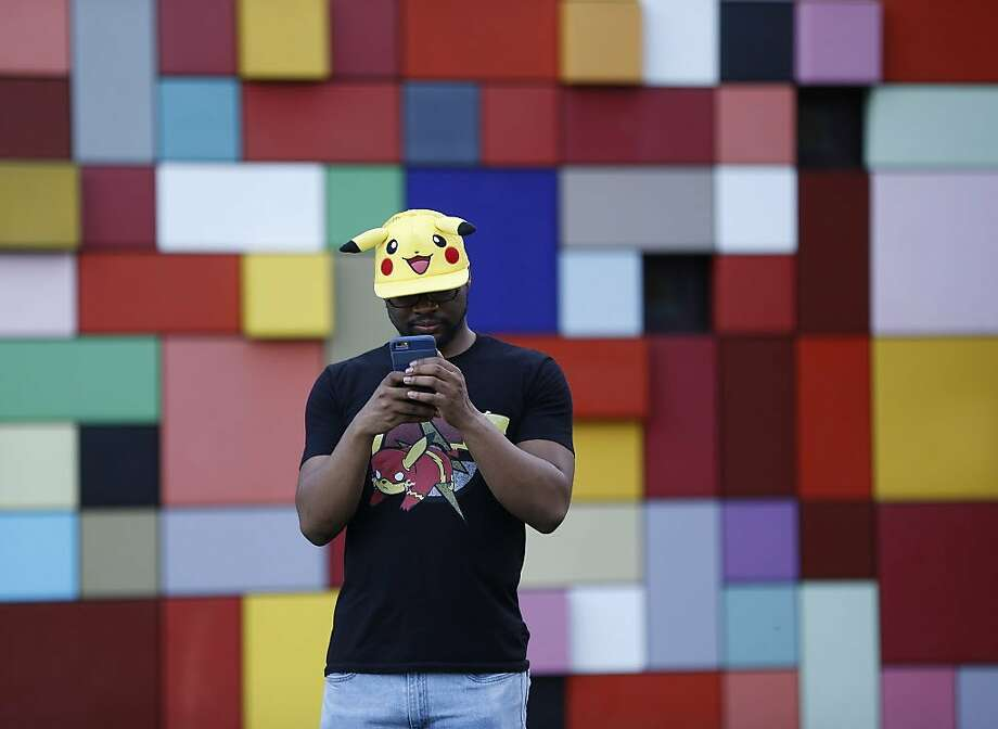 """Michael Simeon, 30, of New Jersey, wears a Pokemon hat and t-shirt while playing Pokemon Go, in Discovery Green, which is a """"gym"""", a place where Pokemon players can battle for ownership, Wednesday, July 13, 2016, in Houston. . Gyms attract more players to them, more than other parts of the city, where hundreds have been showing up each night since the Pokeman app started, last week.  ( Karen Warren  / Houston Chronicle ) Photo: Karen Warren, Houston Chronicle"""