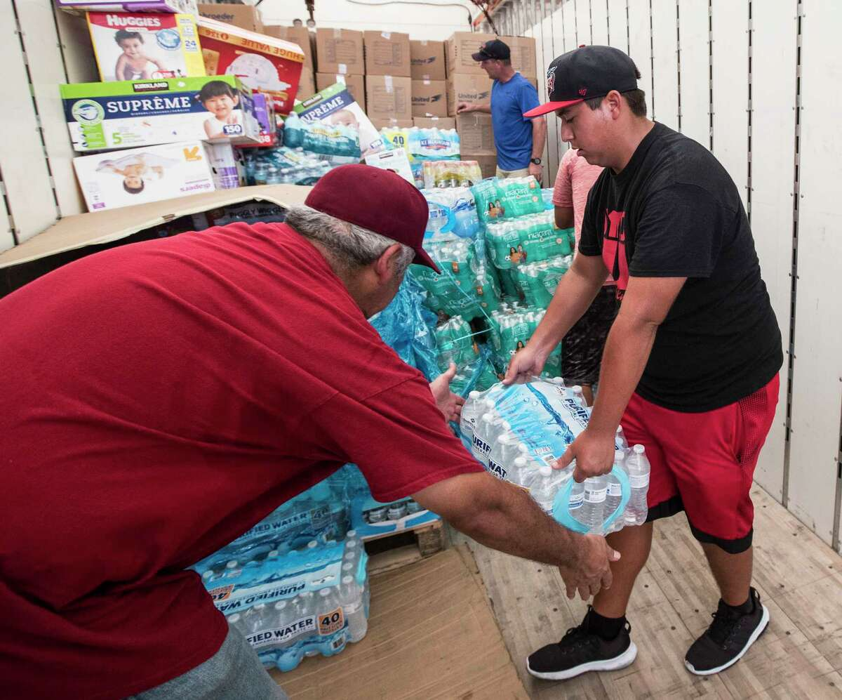Volunteers unload a truck of relief supplies for people impacted by Hurricane Harvey on Sunday in Houston. ( Brett Coomer / Houston Chronicle, POOL )