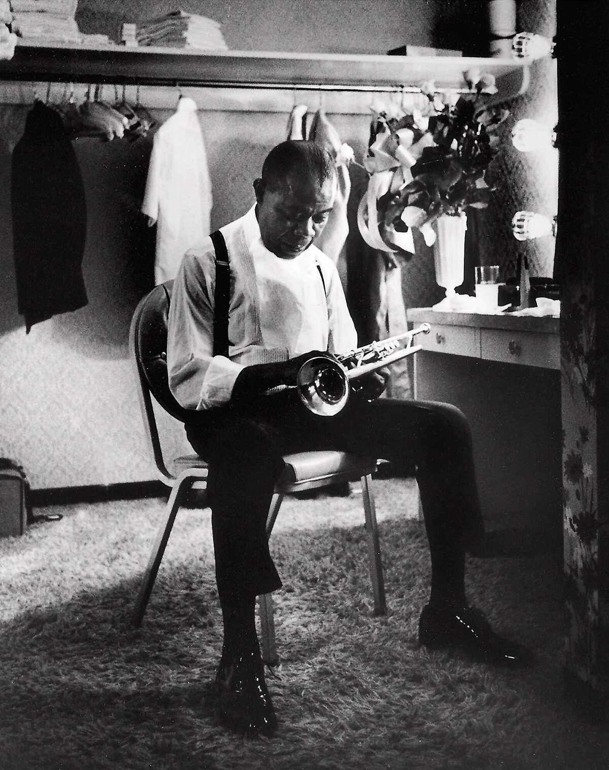 ADVANCE FOR WEEKEND EDITIONS, JUNE 29-JULY 2--FILE--Jazz great Louis Armstrong spends a quiet moment with his trumpet in a Las Vegas dressing room in this September 1970 file photo. Armstrong fans will celebrate the centennial of the day Satchmo claimed for his birthday on July 4, 2000. (AP Photo/Eddie Adams, File)