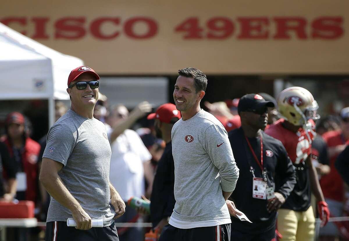 San Francisco 49ers head coach Kyle Shanahan, center, laughs with general manager John Lynch during an NFL football training camp in Santa Clara, Calif., Saturday, Aug. 5, 2017. (AP Photo/Jeff Chiu)