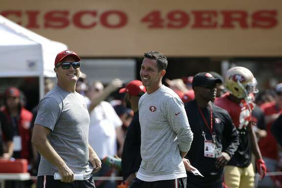 San Francisco 49ers head coach Kyle Shanahan, center, laughs with general manager John Lynch during an NFL football training camp in Santa Clara, Calif., Saturday, Aug. 5, 2017. (AP Photo/Jeff Chiu)