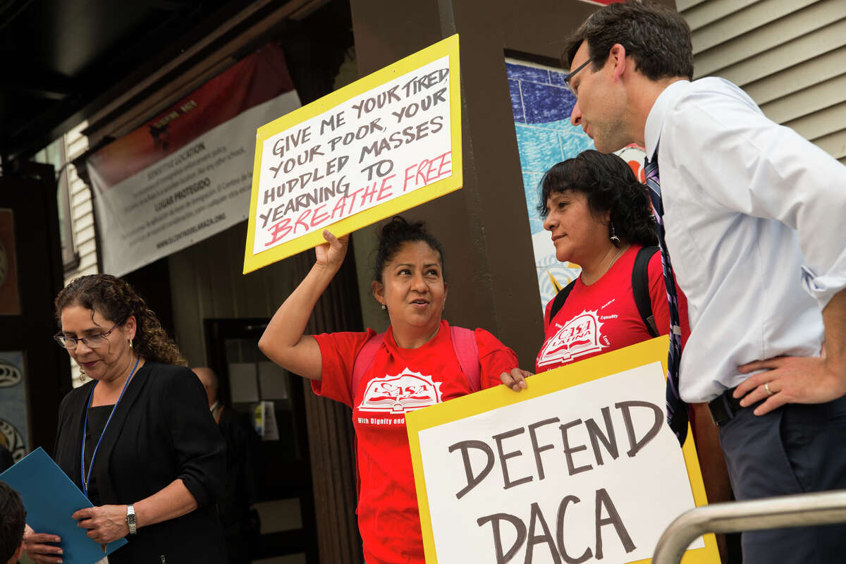 Washington Attorney General Bob Ferguson speaks with Casa Latina representatives during a rally against President Trump's decision to end DACA at El Centro De La Raza.