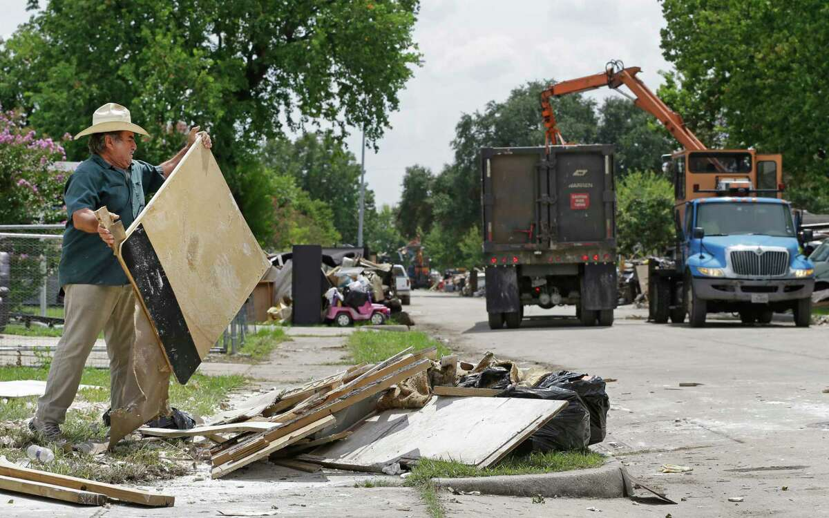 Advento Lopez, Sr., 71, works to move debris closer to the street as City of Houston crews remove debris along Terminal St. in the Denver Harbor neighborhood Tuesday, Sept. 5, 2017, in Houston. Crews had removed much of pile infront of the home but the rest of the debris had to moved closer for the machine to reach the pile. Much of the area was flooded in the aftermath of Hurricane Harvey. ( Melissa Phillip / Houston Chronicle )