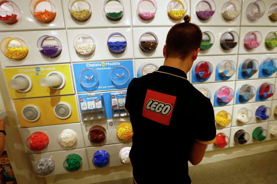 FILE- In this Tuesday, April 5, 2016 file photo, an employee sorts Legos in the the new LEGO flagship store unveiled as part of the new Les Halles shopping mall during the press visit in Paris. Danish toy maker Lego said Tuesday, Sept. 5, 2017, it will cut 1,400 jobs, or about eight percent of its global workforce, after reporting a decline in sales and profits in the first half of 2017. (AP Photo/Francois Mori, File) Photo: Francois Mori, STF / Copyright 2017 The Associated Press. All rights reserved.