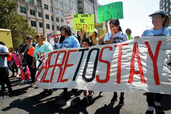 Cielo Mendez, 17, of Plainfield, N.J., who is a DACA recipient, second from left with banner, marches next to Gabriel Henao, 7, and Kimberly Armas, 15, of Elizabeth, N.J., in support of the Deferred Action for Childhood Arrivals program, known as DACA, outside of Immigration and Customs Enforcement (ICE), in Washington, Tuesday, Sept. 5, 2017. President Donald Trump plans to phase out the DACA program that has protected hundreds of thousands of young immigrants brought into the country illegally as children and call for Congress to find a legislative solution. (AP Photo/Jacquelyn Martin)