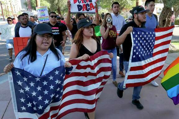 Deferred Action for Childhood Arrivals (DACA) supporters march to the Immigration and Customs Enforcement office to protest shortly after U.S. Attorney General Jeff Sessions' announcement that the Deferred Action for Childhood Arrivals (DACA), will be suspended with a six-month delay, Tuesday, Sept. 5, 2017, in Phoenix. (AP Photo/Matt York)