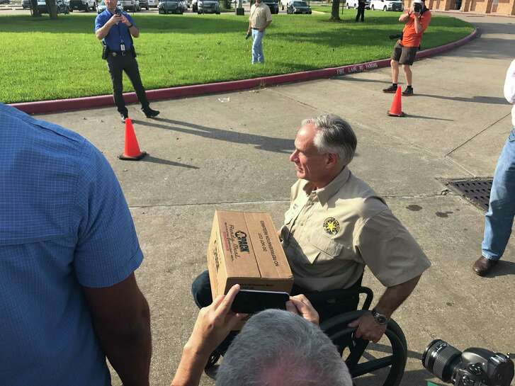 Gov. Greg Abbott helps hand out meals in Beaumont on Tuesday, September 5, 2017.