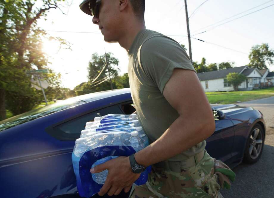 U.S. Army branch 3-133 soldier Juan Retana loads up a box of bottled water into a motorist's vehicle outside Babe Zaharias Memorial Stadium Monday, Sept. 4 2017, in Beaumont, Texas. Beaumont residents are without running water due to flooding that affected a water pipeline after Tropical Storm Harvey. Photo: Godofredo A. Vasquez / Houston Chronicle