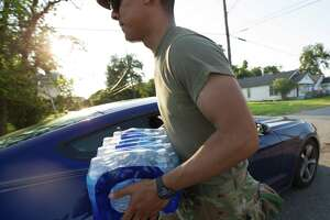 U.S. Army branch 3-133 soldier Juan Retana loads up a box of bottled water into a motorist's vehicle outside Babe Zaharias Memorial Stadium Monday, Sept. 4 2017, in Beaumont, Texas. Beaumont residents are without running water due to flooding that affected a water pipeline after Tropical Storm Harvey.