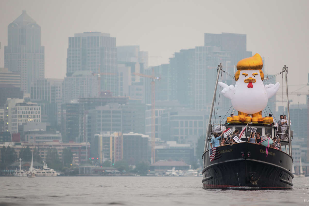 An inflatable Trump chicken aboard a boat approaches Robert Mercer's yacht on Lake Union in Seattle on Tuesday, Sept. 5, 2017.
