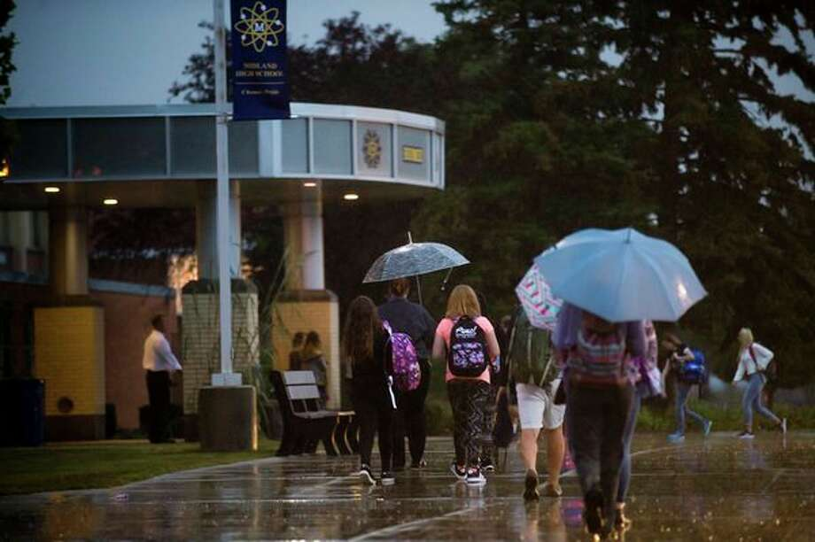 Midland High students walk through the rain on the first day of school Tuesday morning. (Katy Kildee/kkildee@mdn.net)