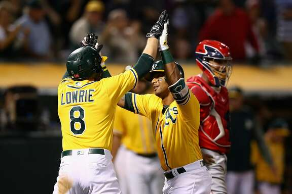 OAKLAND, CA - SEPTEMBER 05:  Khris Davis #2 of the Oakland Athletics is congratulated by Jed Lowrie #8 after he hit a two-run home run off of Blake Wood #46 of the Los Angeles Angels in the fifth inninng at Oakland Alameda Coliseum on September 5, 2017 in Oakland, California.  (Photo by Ezra Shaw/Getty Images)