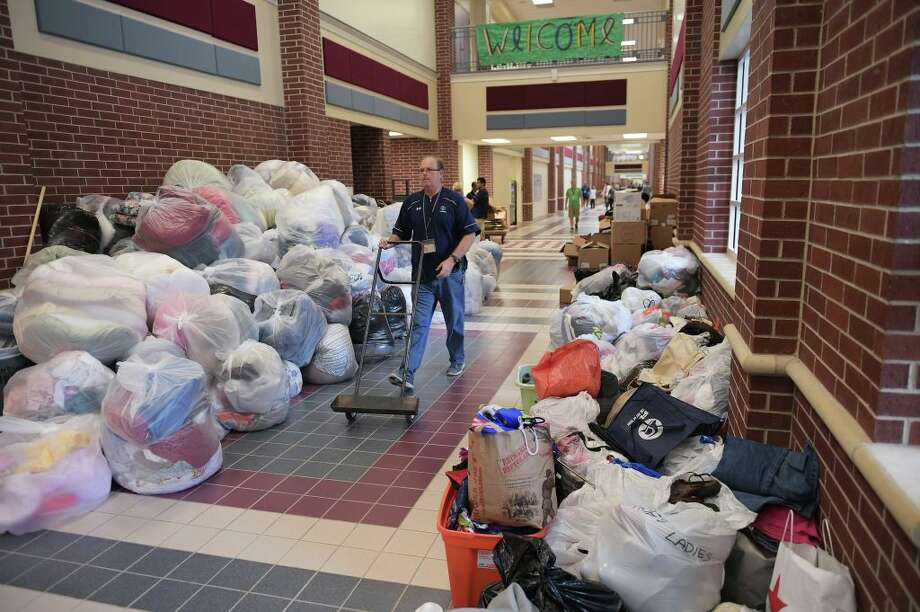 Clothing drenched by Hurricane Harvey flood waters should be thrown due to a risk of mold. Luckily places like the Woodlands' College Park High School, seen above, have been accepting donations of unaffected clothes. Swipe through to see photos of the damage Harvey left behind in Texas. Photo: AFP Contributor/AFP/Getty Images