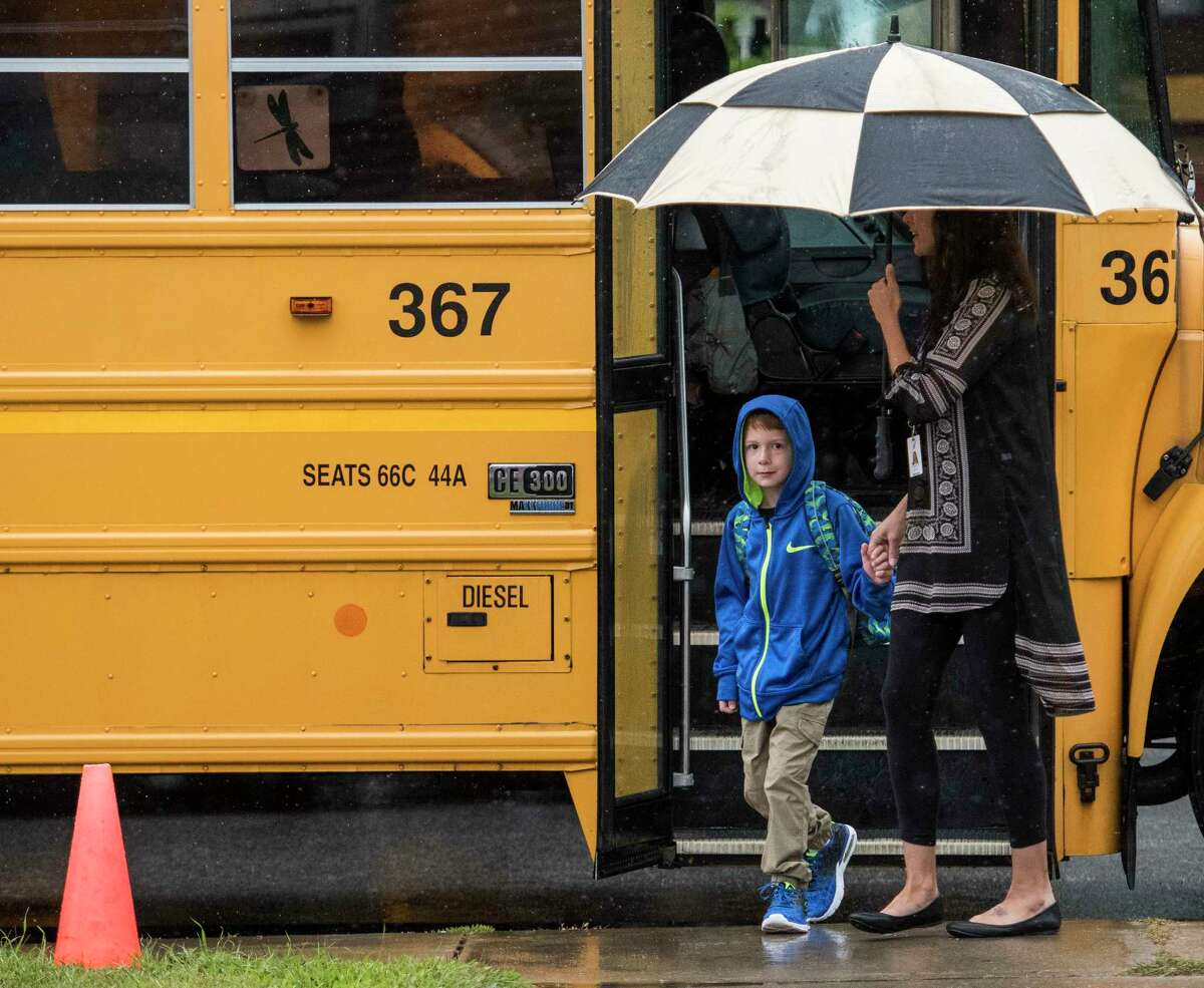 A student is given a little protection from the weather on the first day of school at the Lake Avenue Elementary School on Wednesday, Sept. 6, 2017, in Saratoga Springs, N.Y. (Skip Dickstein/Times Union)